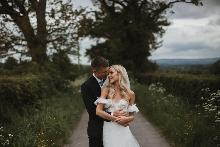Bride in Emma Beaumont Wedding Dress and Groom Embrace In Fields