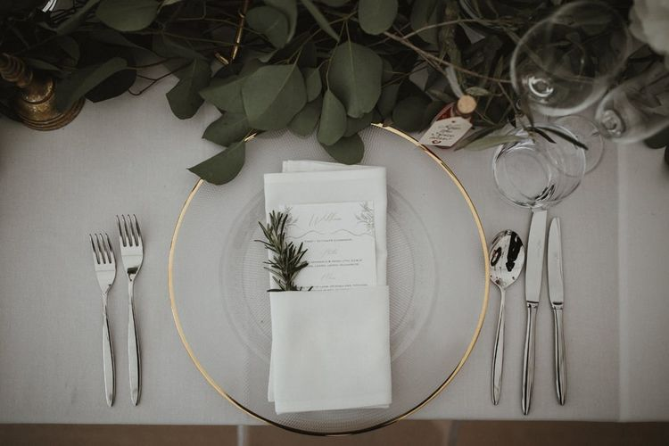 Wedding Table Place Setting With Gold Rimmed Plate and Foliage Decor