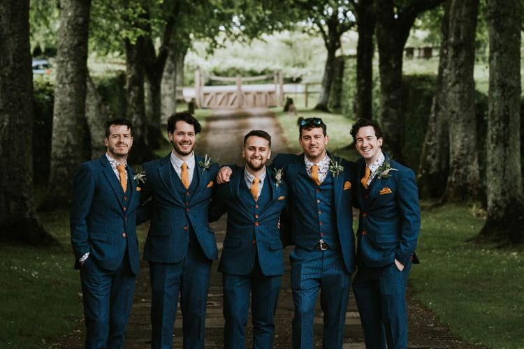 Groom and groomsmen in matching suits with orange ties