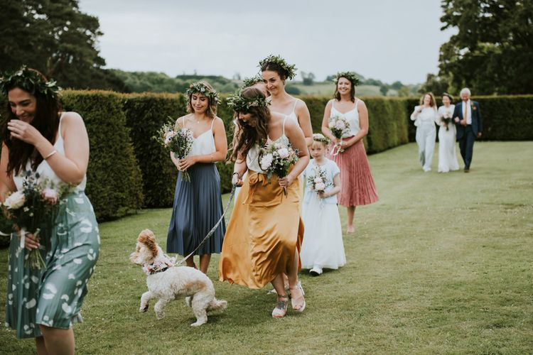 Bridal party and pet dog on their way to outdoor ceremony
