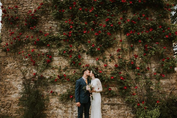 Bride in Savannah Miller wedding dress kisses groom in woolen suit