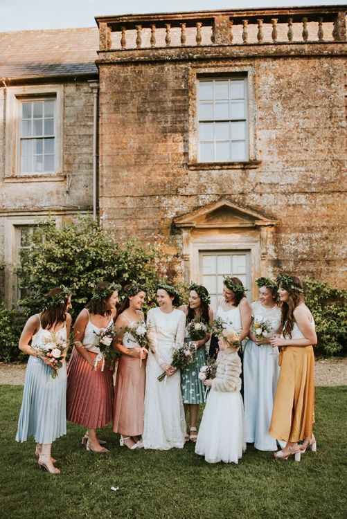 Bridal party in colourful midi skirts with bride in Savannah Miller wedding dress