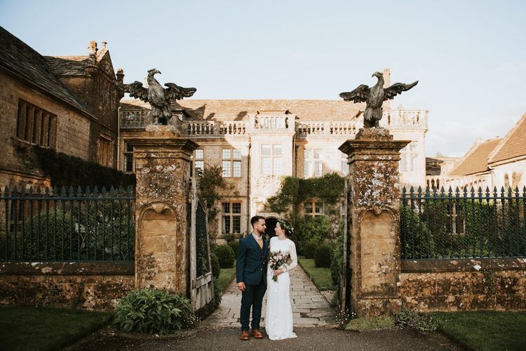 Bride and groom infront of Mapperton House with Savannah Miller wedding dress
