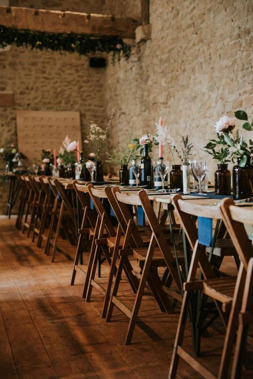 Wedding table decor with flower stems in glass bottles