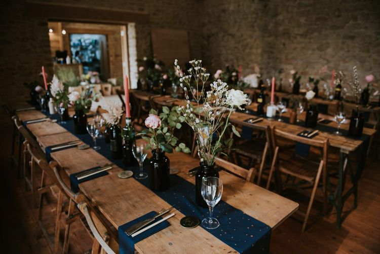 Wedding table decor with flower stems in glass bottles and navy table runners