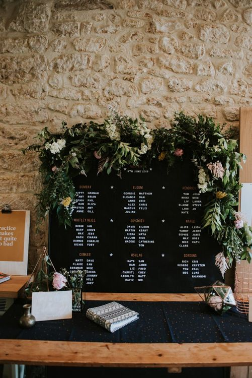 Peg board seating chart with foliage and flower decor