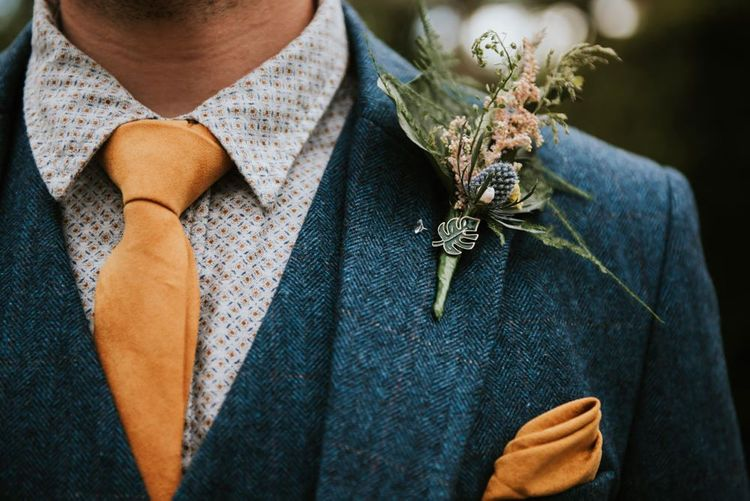 Groom in wooden suit with orange tie and pocket square