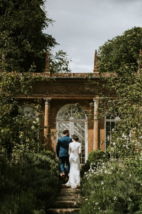 Bride in Savannah Miller wedding dress and groom take stroll through venue grounds in Dorset