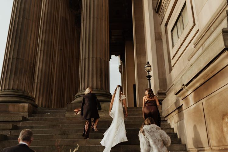Bride arriving at her relaxed wedding ceremony with brown bridesmaid dresses