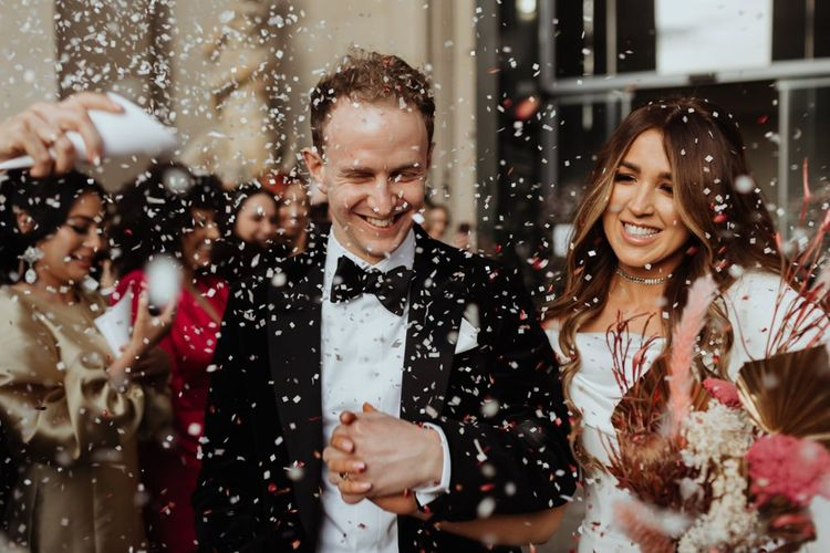 Bride and groom confetti shot at an informal party celebration in Liverpool with brown bridesmaid dresses and pampas grass bouquet
