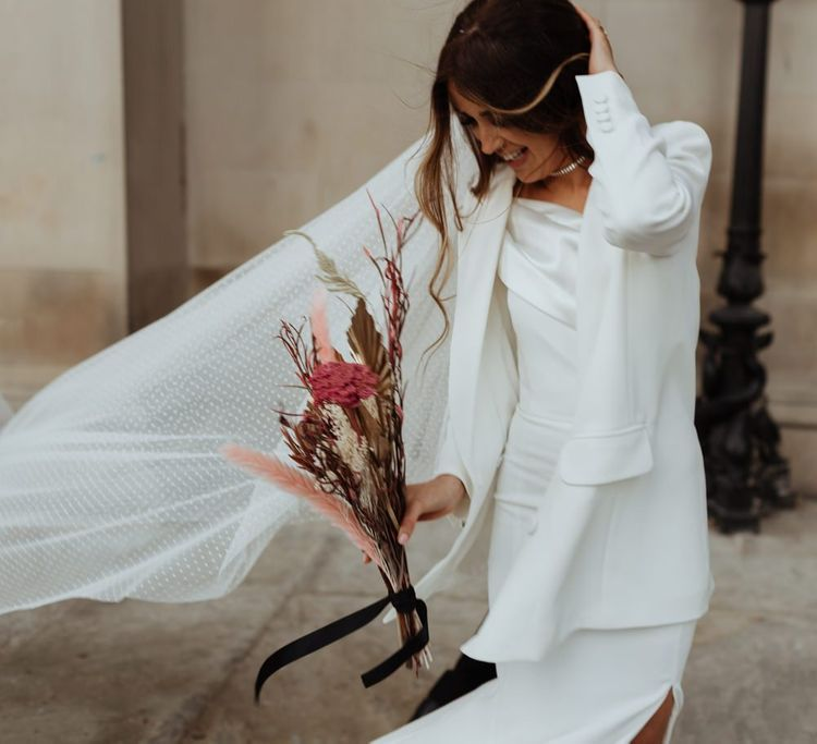 Bride wearing a statement pair of bright pink shoes with a  white blazer and dried pampas grass filled bouquet