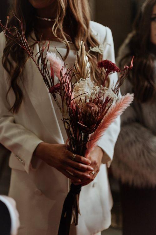Bride wearing a statement  white blazer and dried flower bouquet