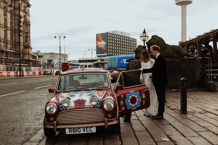 Bride and groom travel in style to their wedding reception in a personalised Mini Cooper