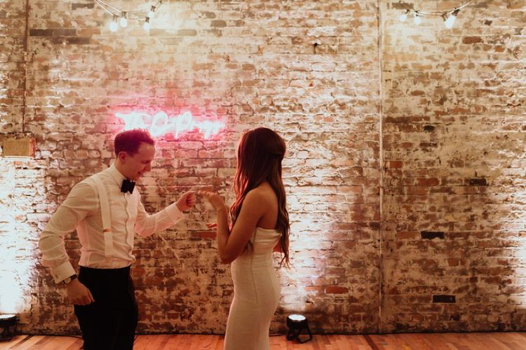 Bride and groom at their industrial styled reception with bare brick walls and a neon sign