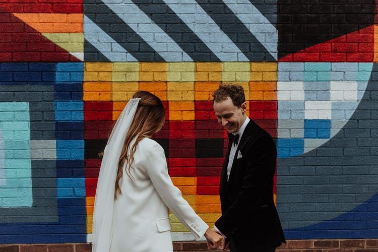 Groom looking dapper in Hugo Boss suit with the bride in a statement blazer and veil