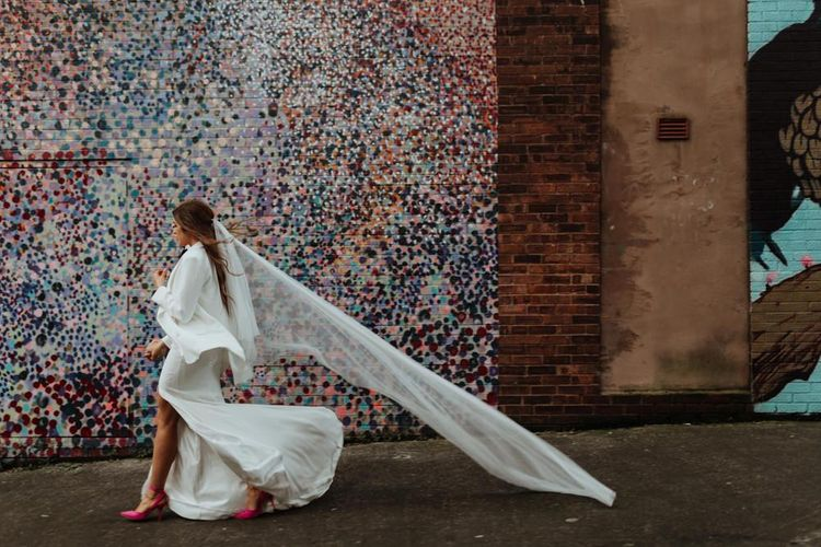 Bride wearing a bespoke dress with a statement pair of pink heels and a white blazer for glam celebration in December