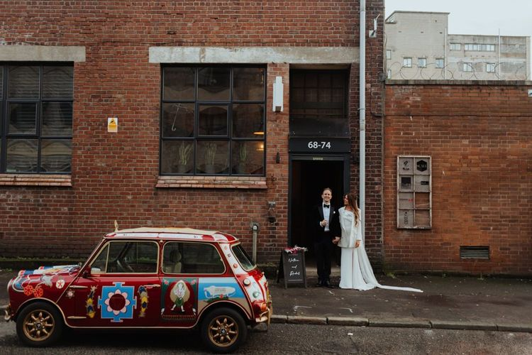 Bride and groom arrive at their reception with personalised Mini Cooper and a statement white bridal blazer