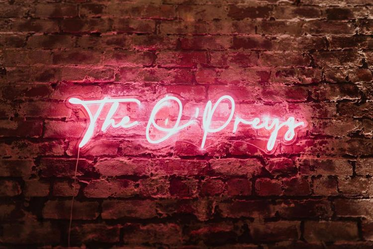 Bright pink neon sign at industrial styled reception with bare brick walls