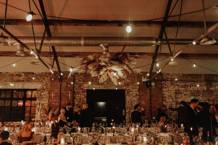 Industrial style warehouse reception with festoon lighting and a pampas grass hanging floral installation