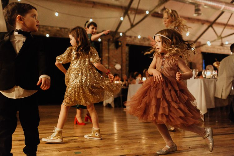 Younger guests enjoying the music at this informal party wedding with festoon lighting and brown bridesmaid dresses