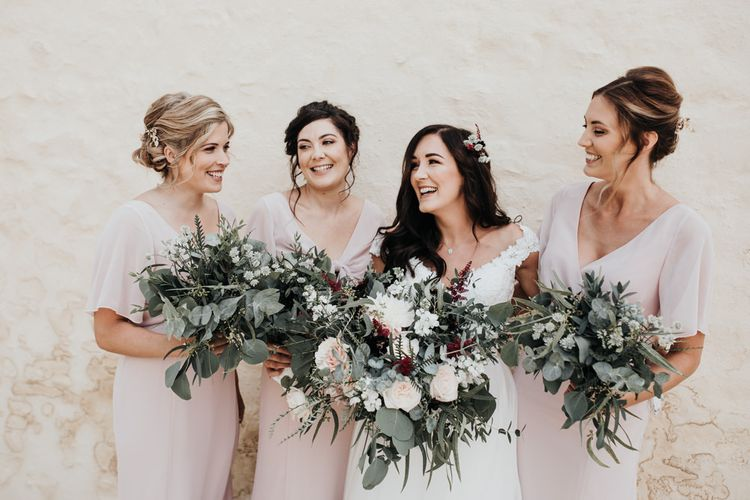 Bride in Paloma Blanca wedding dress with pink bridesmaid dresses
