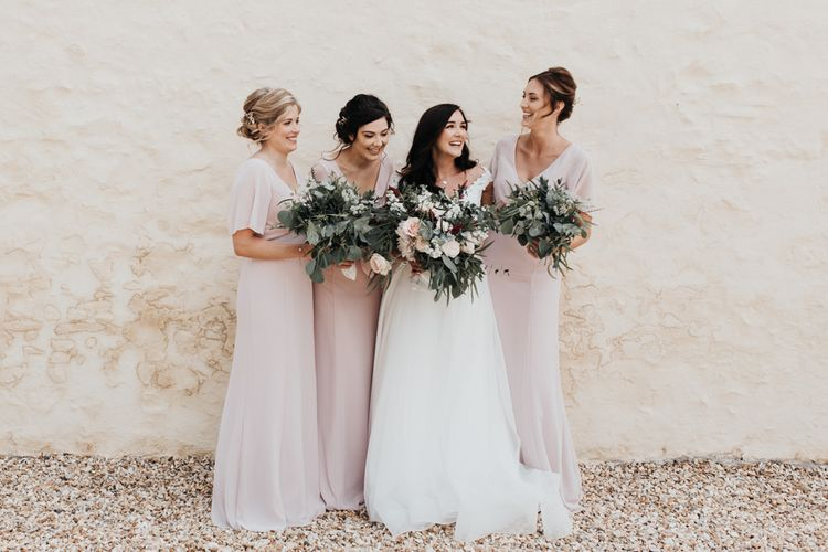 Bride in Paloma Blanca wedding dress with pink bridesmaid dresses and foliage bouquets