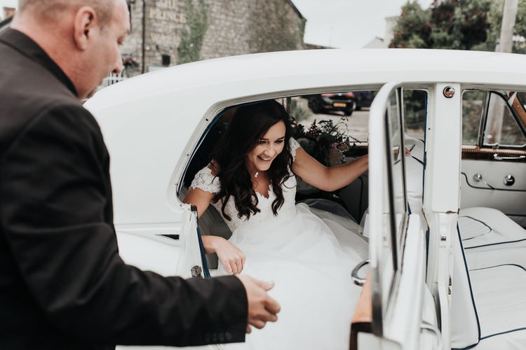 Bride in Paloma Blanca wedding dress gets out of wedding car at church ceremony in South Wales