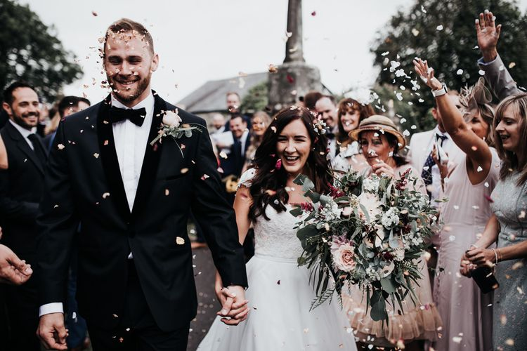 Confetti exit for bride in Paloma Blanca wedding dress with and groom in bespoke tuxedo