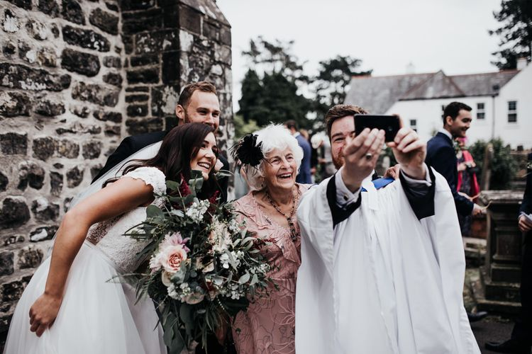 Priest takes a selfie with groom and bride in Paloma Blanca wedding dress