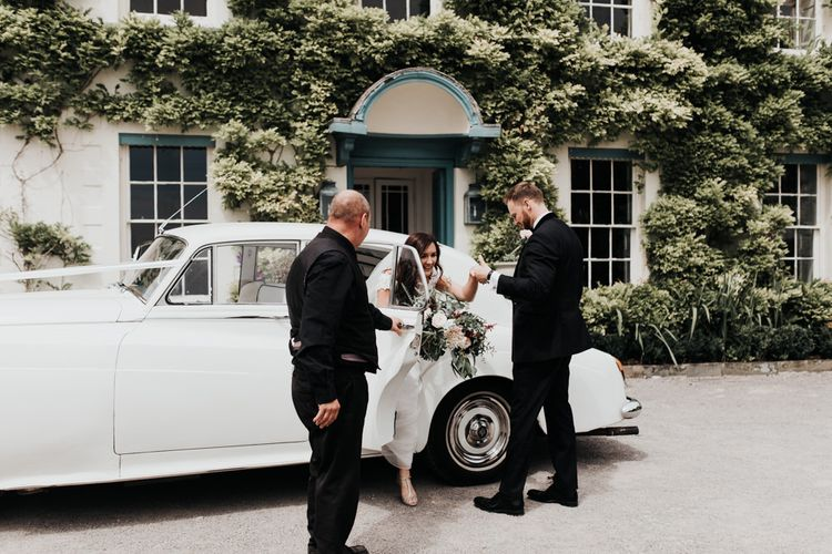 Bride in Paloma Blanca wedding dress arrives with groom in white wedding car