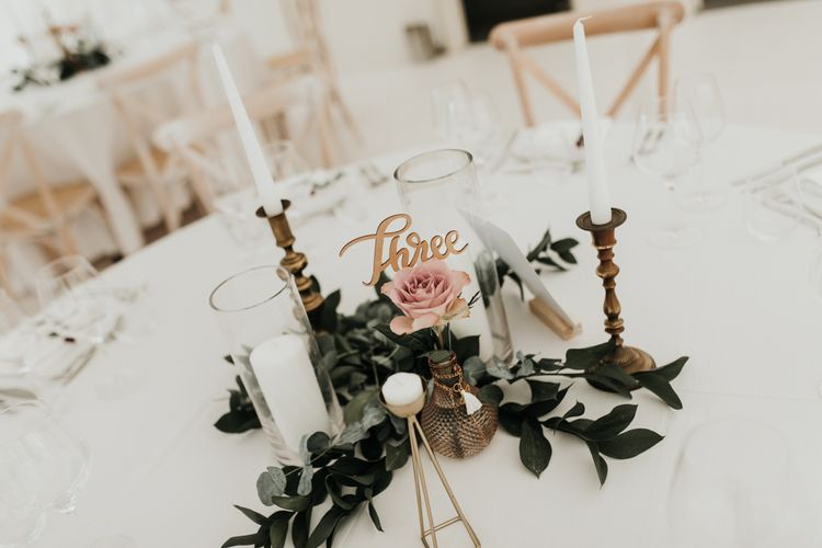 Gold wedding decor detail with pink flowers and foliage