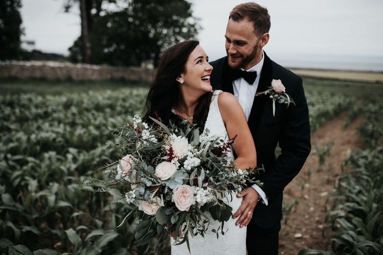 Bride with large foliage and pink flower bouquet