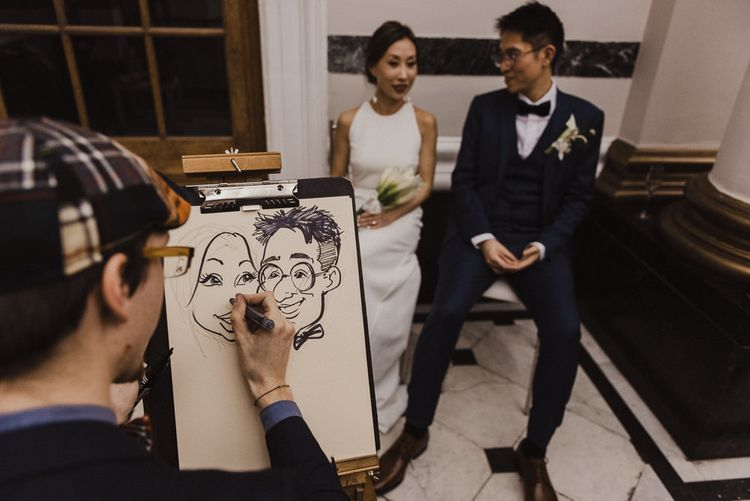 Bride and Groom having a Caricaturist Drawing