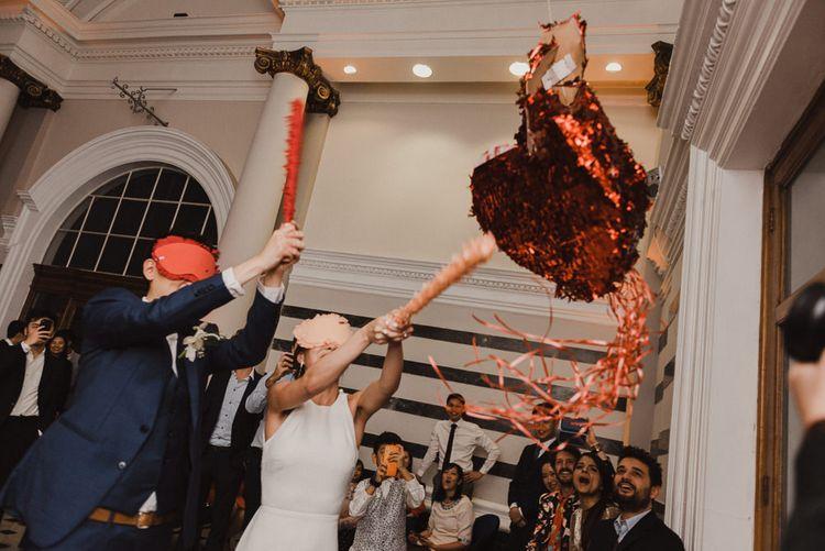 Bride and Groom Hitting a Piñata