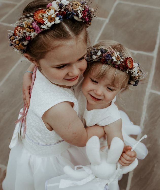Flower girls with dried flower crowns cuddling