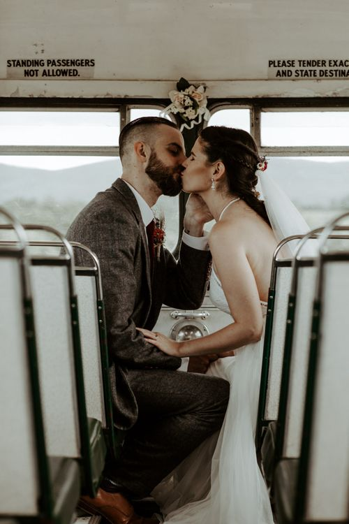 Bride and groom kissing on the wedding bus