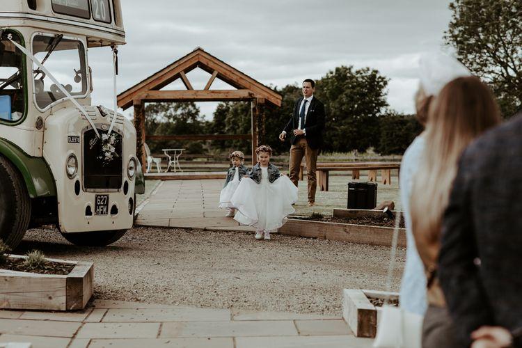 Flower girls in white dresses, denim jackets and dried flower crowns at  Eden Barn wedding