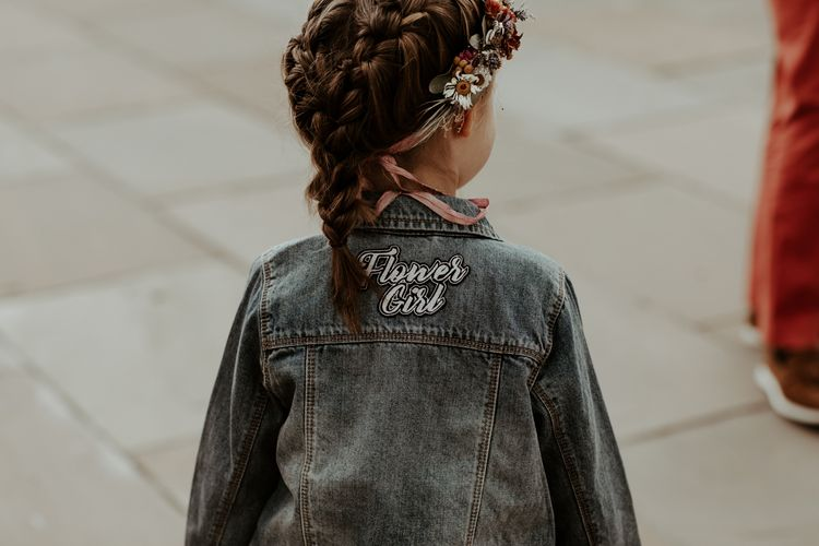 Flower girl with braided up do and customised denim jacket