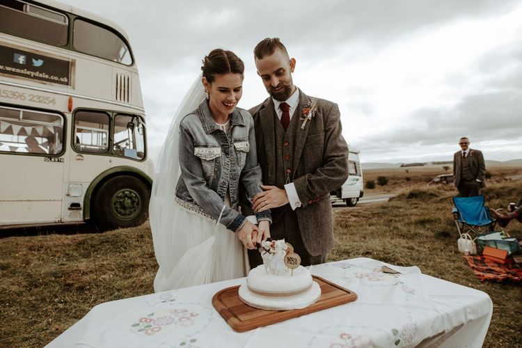 Bride and groom cutting the cake at socially distanced wedding picnic