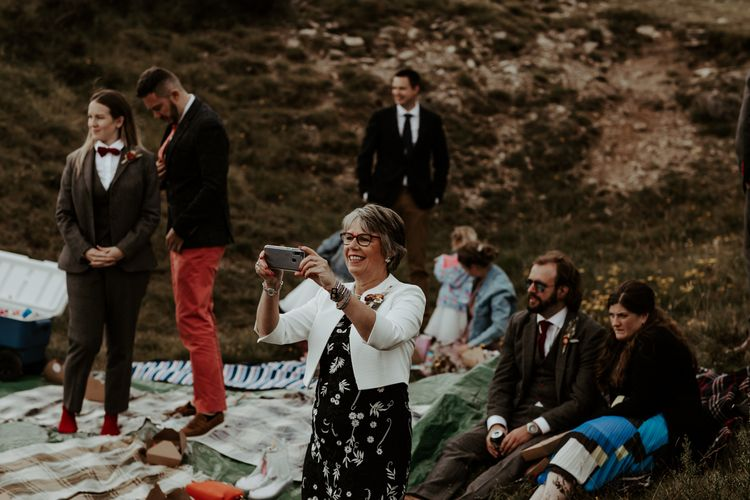 Wedding guest taking a picture on their phone at socially distanced wedding picnic
