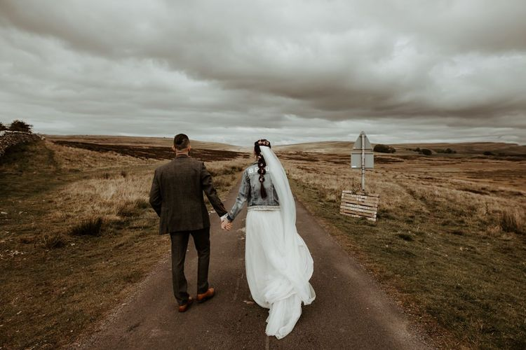 Groom in world suit and Bride in denim jacket walking in the Lake District