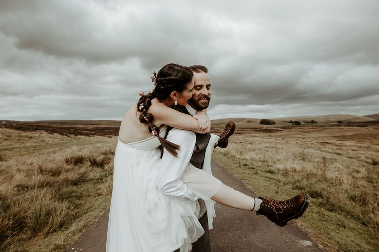 Bride in halterneck wedding dress with boots and braids for Eden Barn wedding