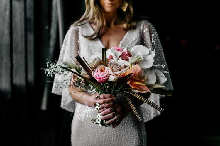 contemporary bouquet with gold sprayed palms, roses, orchids and anthuriums
