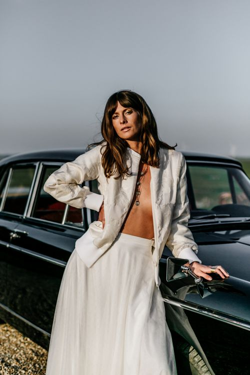 Boho Bride with Sweeping Fringe Leaning Up Against a Wedding Car
