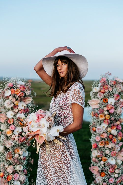 Bohemian Bride in Lace Wedding Dress and Floppy Hat Holding a Blush Pink and white Flower Bouquet