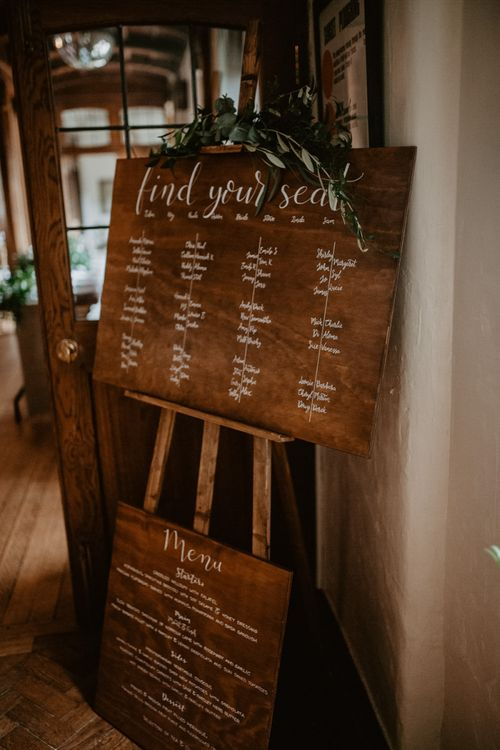 Wooden seating chart and menu sign at Voewood wedding