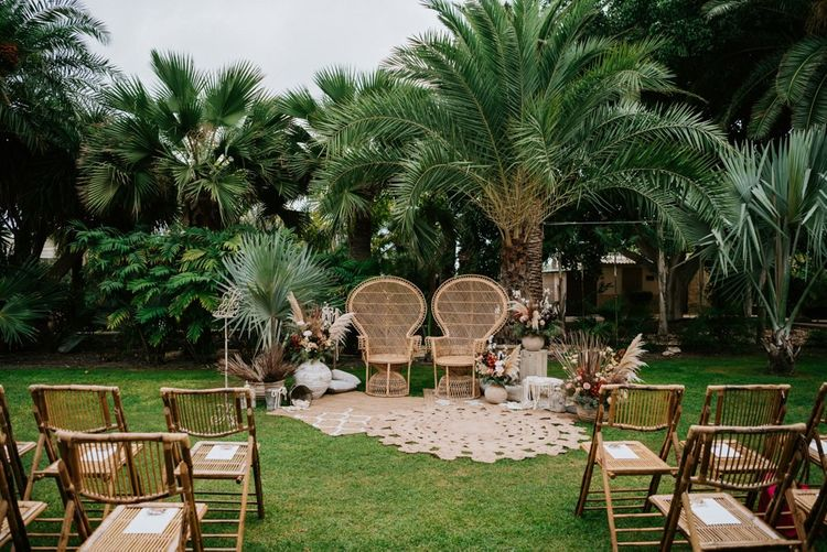 Outdoor wedding ceremony decor with peacock chairs and pampas grass