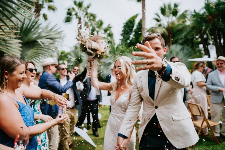 Confetti exit for bride in Made With Love Bridal dress  and groom