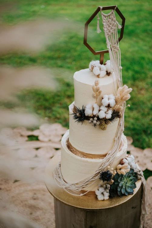 White and gold wedding cake with flowers, pampas grass and macrame