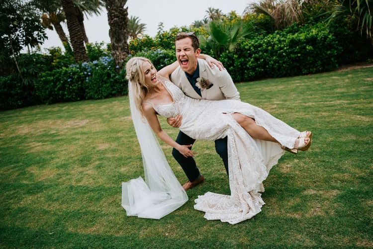 Groom picks up bride in Made With Love Bridal dress